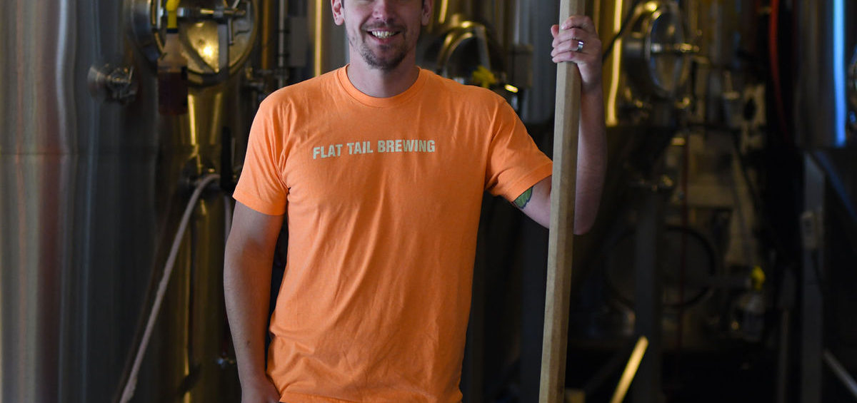 Dave Marliave of Flat Tail Brewing holding mash paddle in front of fermentors