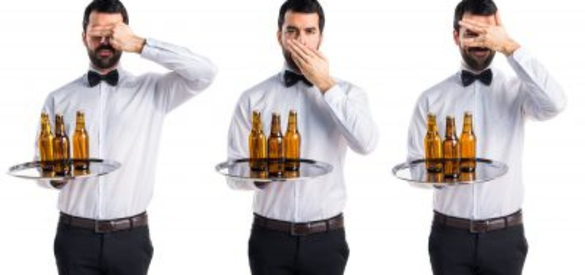 Waiter with beer bottles on the tray covering his mouth