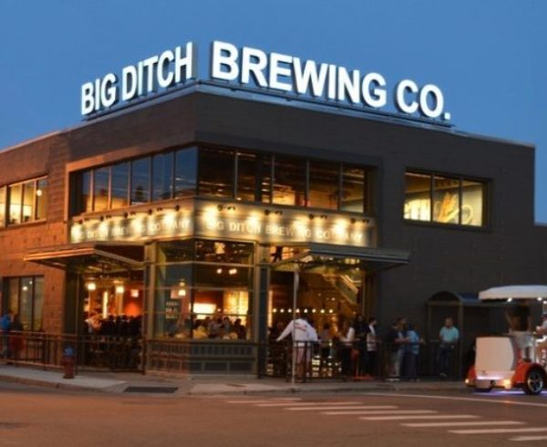Big Ditch Brewing Co.building with sign on top and pedal cart out front