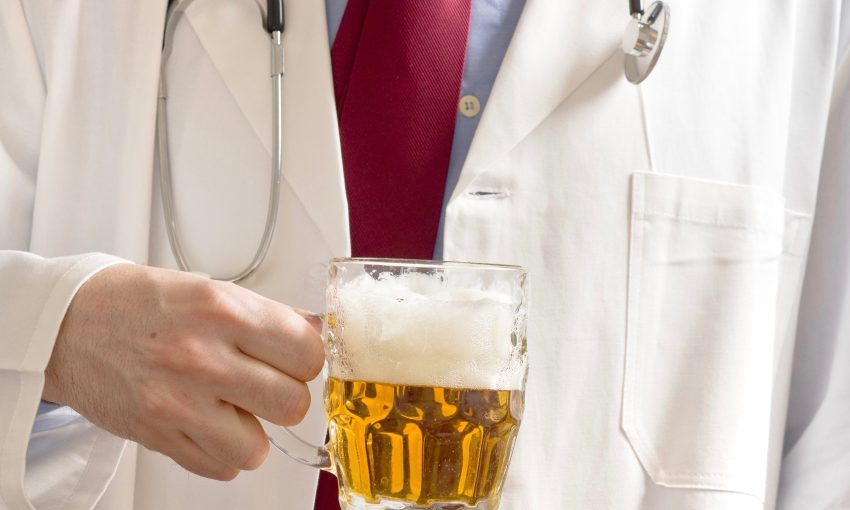 Male doctor is drinking light beer from the glass jug. One glass of beer a day concept.