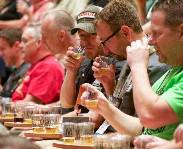 Beer tasting at homebrewcon 2017 with small glasses and line of judges tasting