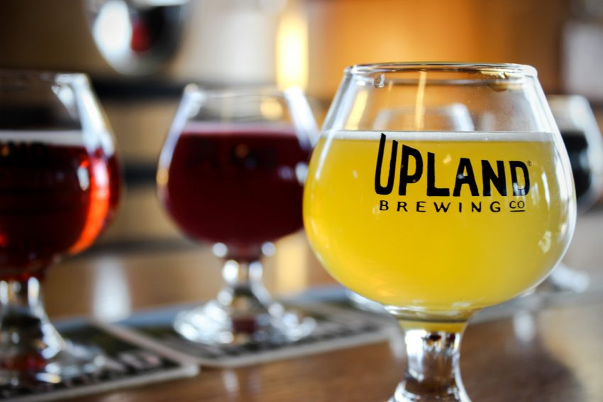 Upland Belgian style glass with logo and yellow colored beer inside