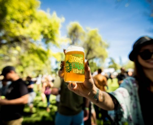 Picture of beer festival glass with Spring Brews Festival logo held up by woman in the park