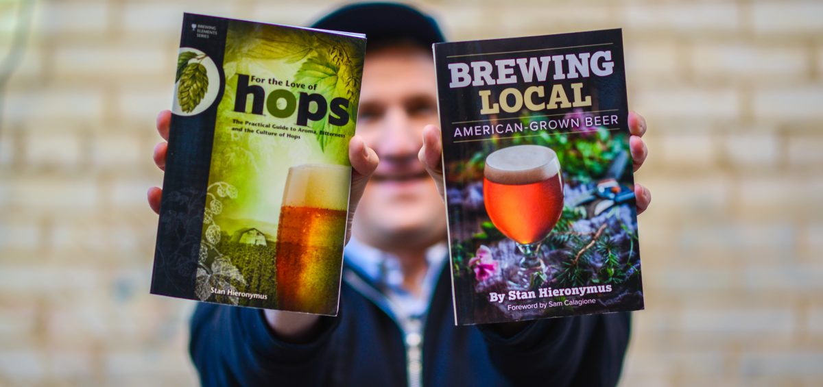 Man holding two books about beer with outstretched arms