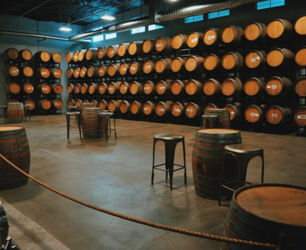 Barrel room with wall of wooden wine barrels and tables