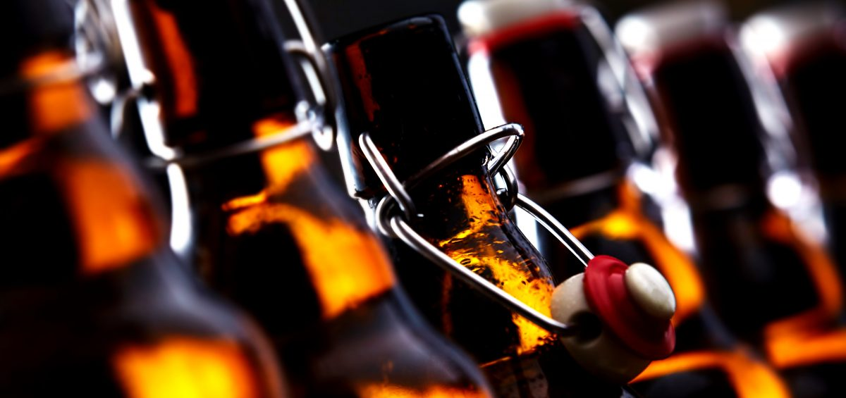 Row of beer bottles with stoppers glowing in the dark with selective focus to the stopper of an open bottle