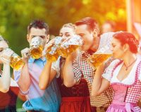 In Beer garden in Bavaria, Germany - friends in Tracht, Dirndl and Lederhosen and Dirndl standing in front of band