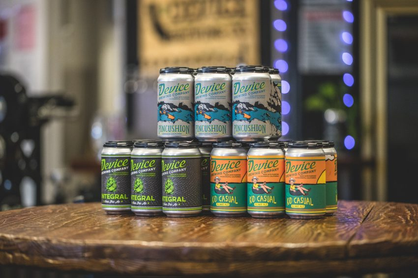 Device Brewing Company cans stacked on table