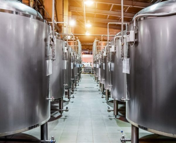 Modern Beer Factory. Rows of steel tanks for beer fermentation and maturation. Spot light effect