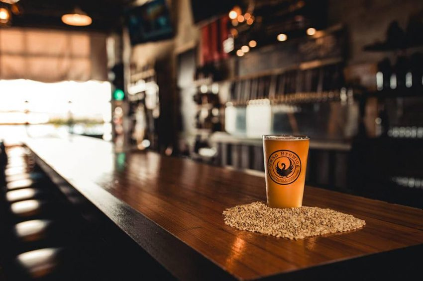 Swan Brewing tasting room with glass on wooden bar top