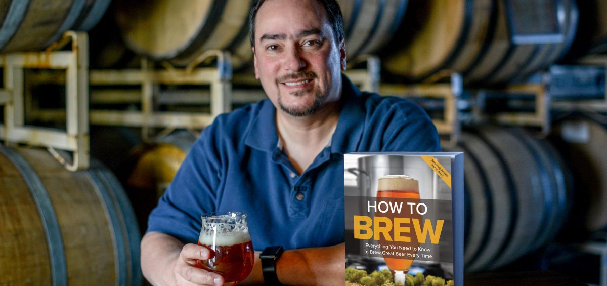 John Palmer, author of How To Brew, at a table in a barrel room with his book and a glass of beer