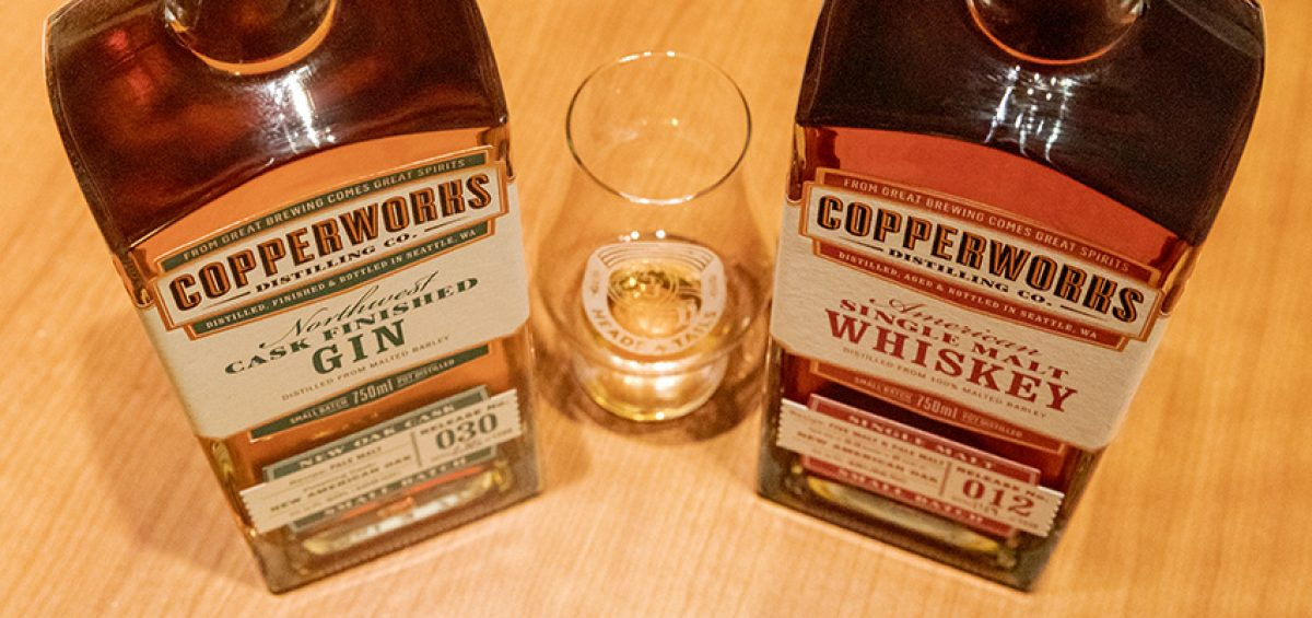 Copperworks spirits sit on a table for Heads and Tails podcast, with a glass in between