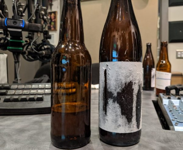 Two bottles of homebrewed beer sit in the studio of Dr. Homebrew