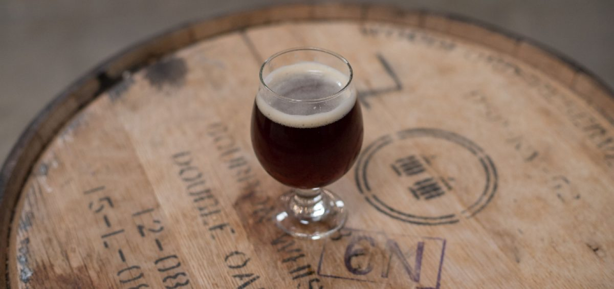 Barrel Aging Beer and beer glass on top of wooden barrel