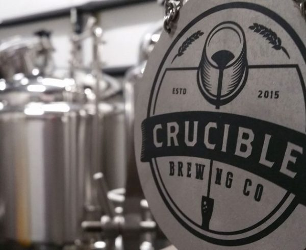 Crucible Brewing logo with brewery in background