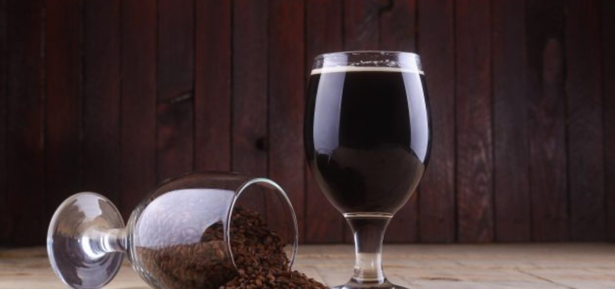 Glass of dark beer and some roasted malt over a wooden background