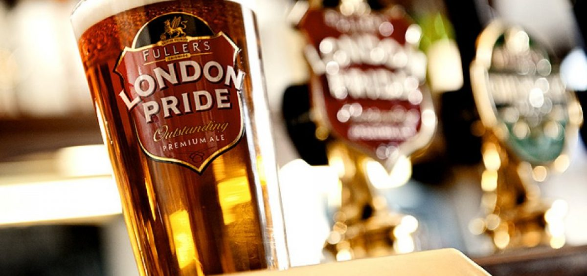 Fullers London Pride Ale in glass with tap handle in background