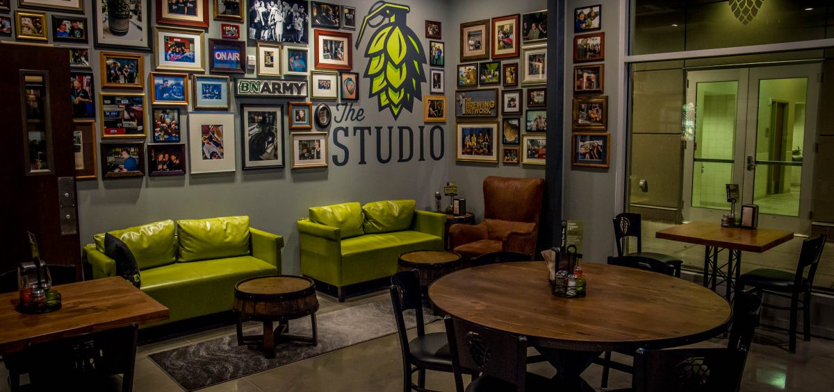 Hop Grenade Fort Collins Studio with pictures on the wall, green couches and wooden tables