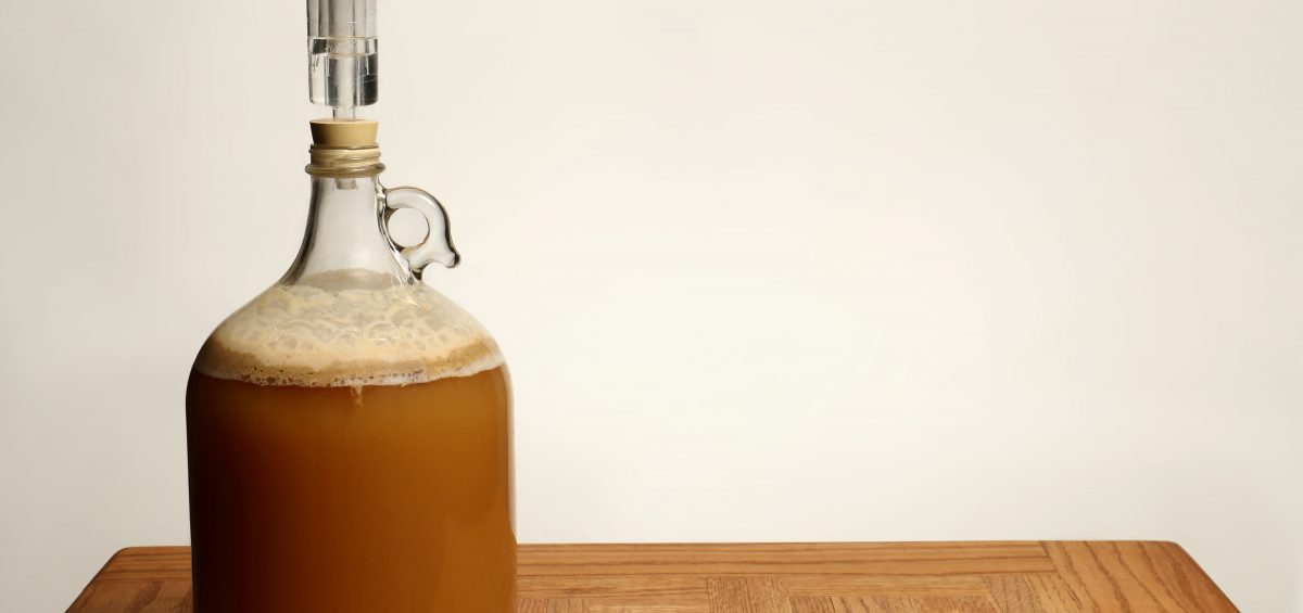 Fermenting Homebrew Beer in glass carboy on table