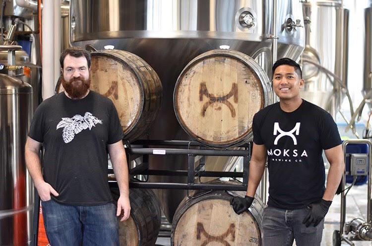 Moksa Head Brewer Derek Gallanosa, and Brewer Cory Meyer standing in front of barrles.