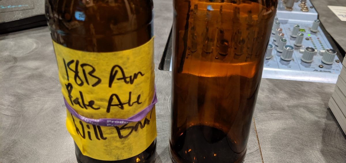 An American Pale Ale bottle and a Pilsner bottle are on the desk of the Dr. Homebrew podcast