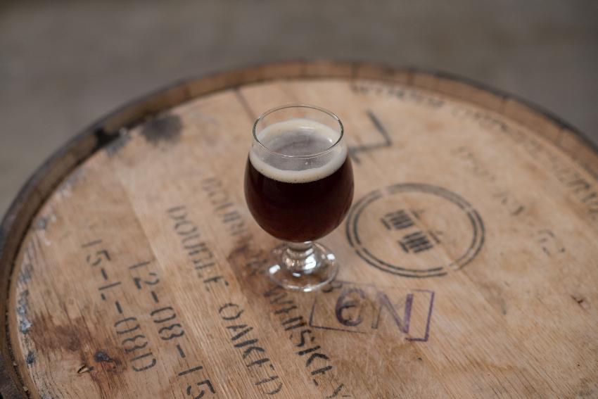 Barrel Aging Beer and beer glass on top of wooden barrel